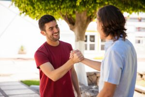 Pair of male friends greeting each other with a handshake